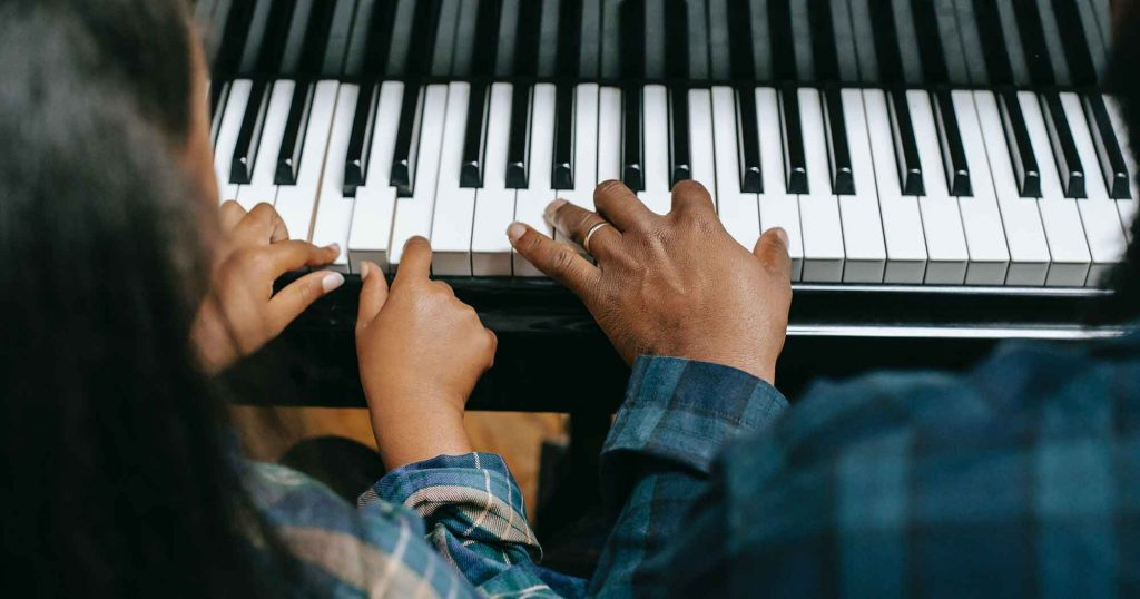 Student learns to play the piano during their music education