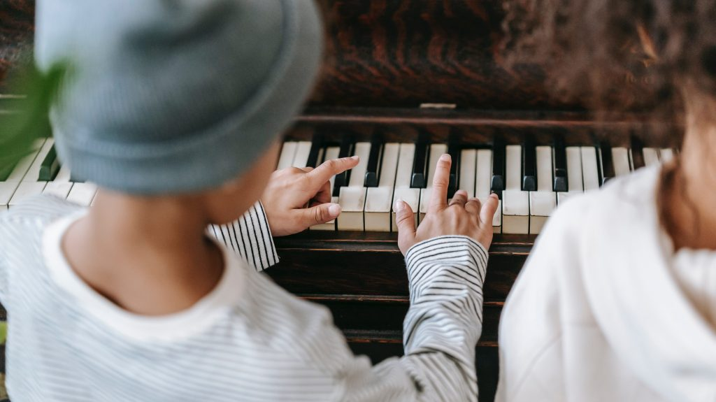 2 small children play the piano