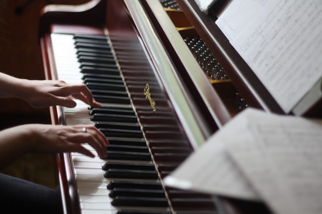 Musician playing the piano whilst preparing for a graded music examination