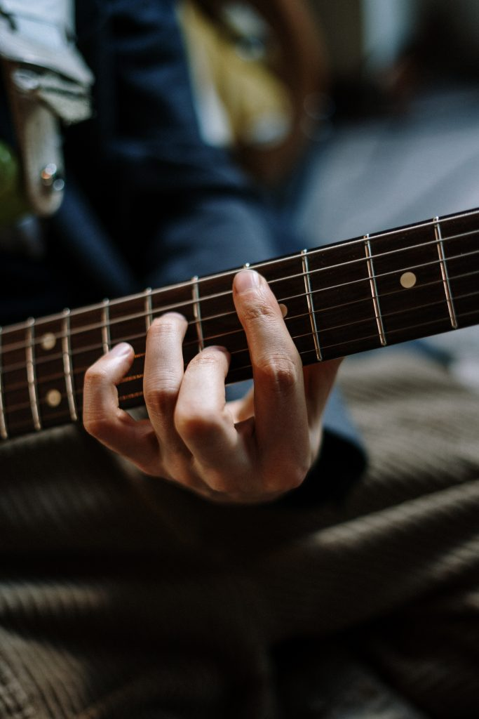 Guitar fret board, with a student holding a chord position to show a music teacher