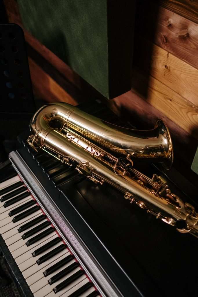 Saxophone lying on top of a piano