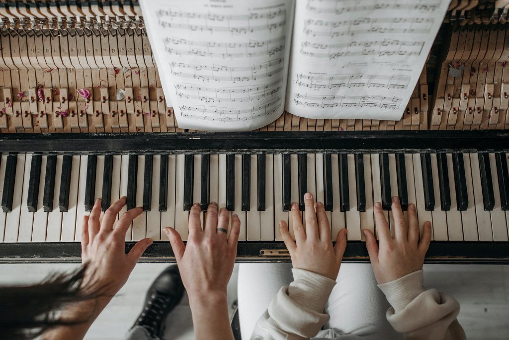 A music teacher's hands and a student's hands playing the piano