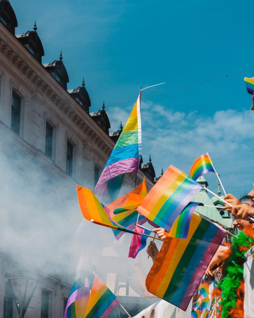 LGBTQ+ pride flags being waved