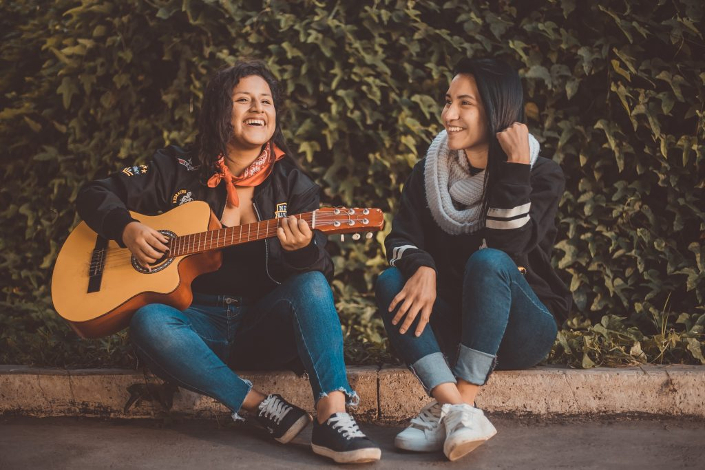 2 people sat together playing a guitar and singing