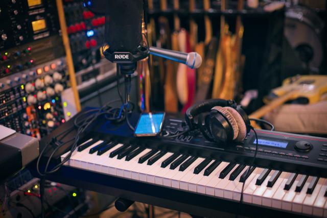 Music studio with keyboard, mics and headphones.