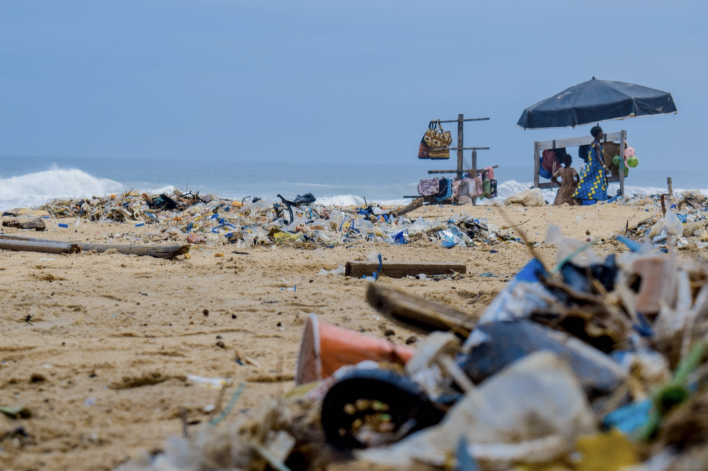 A photo of a beach covered in trash